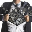 Businessman showing a superhero suit underneath machinery metal gears idea concept — Stock Photo #50331471