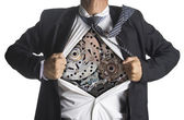 Businessman showing a superhero suit underneath machinery metal gears idea concept — Stock Photo