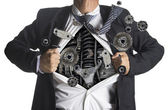Businessman showing a superhero suit underneath machinery metal gears idea concept — Zdjęcie stockowe