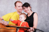 Happy young parents and little baby with guitar — Stock fotografie