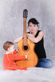 Mother teaches child playing guitar — Stock Photo