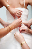 Woman hands help the bride to button the elegant wedding dress — Zdjęcie stockowe
