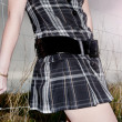 Stock Photo: Portrait of girl with pleated skirt in field body part.