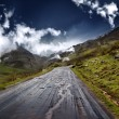 Mountain road. Road between mountains with trees and blue sky — Stock Photo