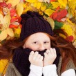 Freckled girl in leaves — Stock Photo