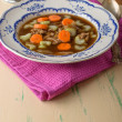 Chicken soup on old vintage table with carrots and selery on top — Stock Photo