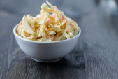 Coleslaw in a bowl on a wooden table — Stock Photo