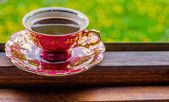 Coffee cup in window with green medow in the background relax fr — Stock Photo