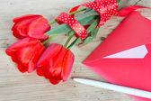 Bouquet of red tulips & envelope  wooden background. — Stock Photo
