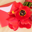 Bouquet of red tulips & envelope with pen on wooden background. — Foto de Stock