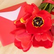 Bouquet of red tulips & envelope with pen on wooden background. — Stok fotoğraf