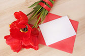 Red tulips bouquet with white paper card&envelope on wooden tabl — Stock Photo