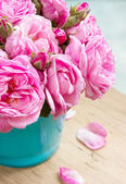 Bouquet of roses in vase on wooden table closeup. — Stock fotografie