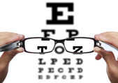 Glasses in hands in front of eye test — Stock Photo