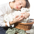 Young girl hugging a lot of white rabbits — Stock Photo