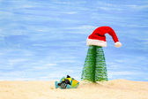 Fish, Christmas tree and red Santa Claus hat — Stock Photo