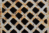 Rusty grate in the sidewalk — Stock Photo