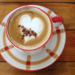 Stock Photo: Hot coffee with latte art in heart shape on wood background