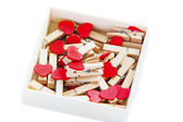 Groups of heart-shaped clothes pin in a box on white — Stock Photo