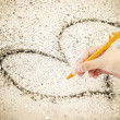 Hand writing with pen on sand background — Stock Photo #47487687