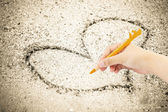 Hand writing with pen on sand background — Stock Photo