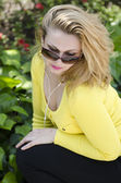 Portrait of a beautiful young woman in a yellow dress and sunglasses. — Stock Photo