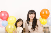 Young woman of Asian appearance and her daughter. — Stock Photo
