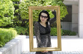 Young girl of the European appearance in sunglasses posing with a picture frame. — Stock Photo