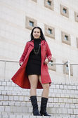 Young beautiful girl in a black dress and a red raincoat . — Stok fotoğraf