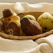 Overripe pears in a bowl cream fabric — Stock Photo