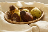 Overripe pears in a bowl cream fabric — Stok fotoğraf