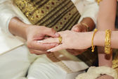 Thai groom wearing wedding ring for his bride  hand — ストック写真