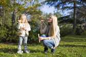 Beautiful mother and daughter with soap bubbles — Stock Photo