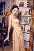 Beautiful girl with black hair in beige silk dress — Stock Photo