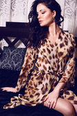 Beautiful girl with black hair in leopard print robe — Stock Photo