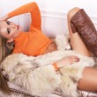 Beautiful girl with blond hair in fur coat lying on sofa — Stock Photo #39835175