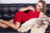 Sexy girl in red dress lying on the black leather divan — Stock Photo
