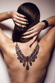 Portrait of woman with naked back with jewelry — Stock Photo