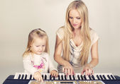Little cute girl with her mom playing on synthesizer — Stock Photo