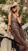Sexy blond woman  in leopard dress with sunglasses — Stock Photo
