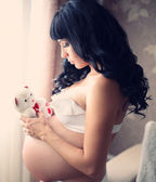 Beautiful pregnant brunette woman with teddy bear — Stock Photo