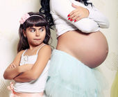 Funny little girl with her pregnant mother — Stock Photo