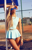Sexy blond woman in blue dress and aviator sunglasses — Stock Photo