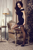 Sexy model with black hair in elegant dress  and pantyhose posing at bedroom — Stock Photo