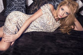 Sexy woman with blond hair in beige sequin dress lying  on the bed — Stock Photo