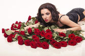 Beautiful woman with dark curly hair with bouquet of red roses — Stock Photo