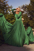 Beautiful woman with blond hair in elegant dress posing at summer park — 图库照片
