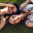 Two beautiful girls lying on a grass at summer garden — Stock Photo