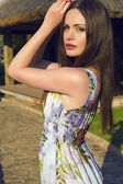Beautiful woman with dark hair and blue eyes posing at summer garden — Stockfoto