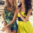 Two beautiful glamour women in colorful dresses on beach — Stock Photo #48691191
